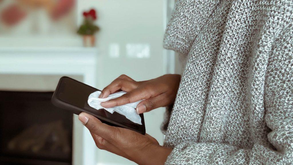 женщина вытирает салфетку на телефоне, как это дезинфицировать телефон