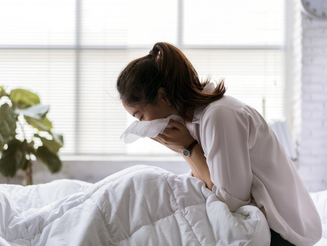 Женщина в постели кашляет.  Симптомы туберкулеза включают сильный кашель, боль в груди и одышку.