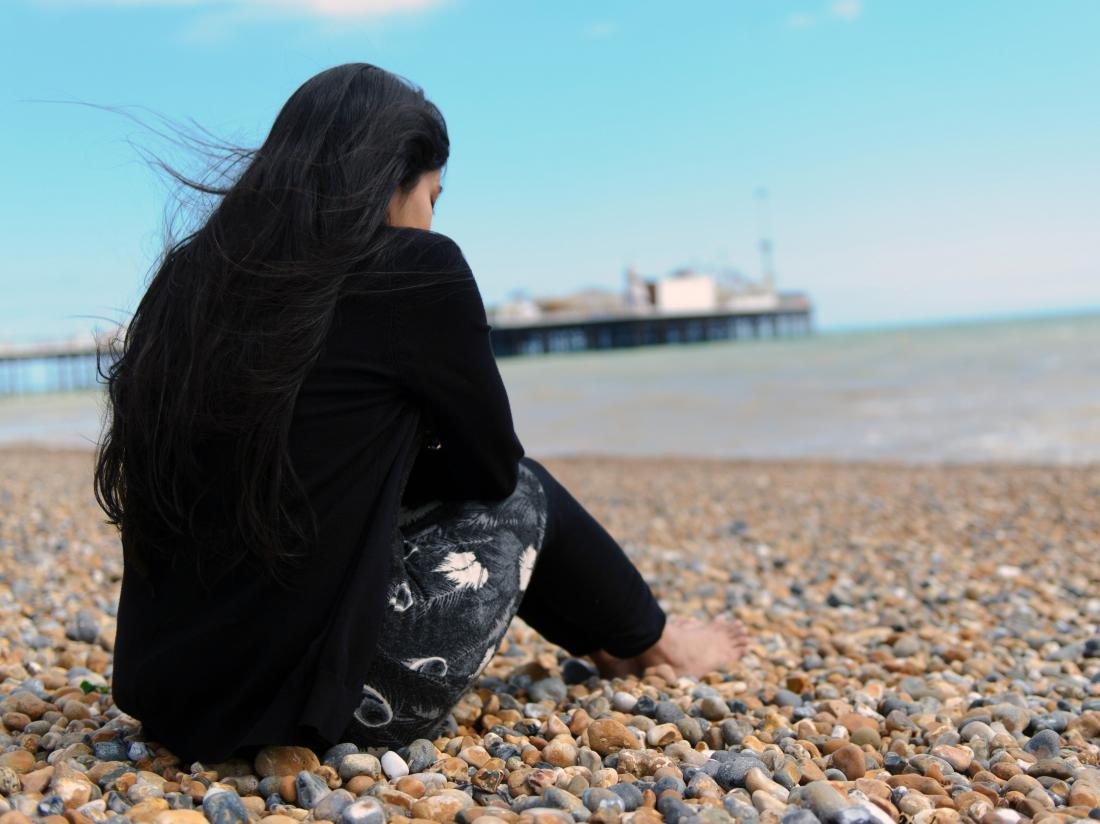 a woman looking depressed sat on a beach.