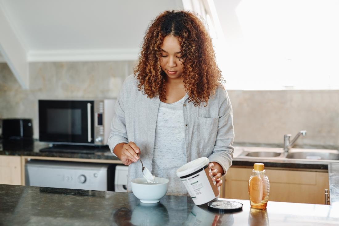 Женщина наливает йогурт